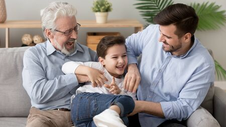 Happy funny multi three 3 generation men family old senior grandfather, young grown son father and cute little child boy grandson laughing playing tickling sit on sofa in living room at home together