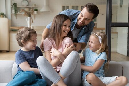 Playful happy young man with children tickling laughing wife mother at modern studio living room at home. Overjoyed millennial woman playing with smiling husband and little kids siblings at home. Stock Photo