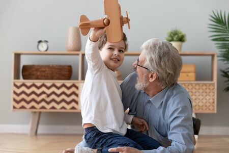 Happy two 2 generation family old grandfather and cute little child boy grandson play hold wooden toy plane lay on floor, funny small grandkid having fun with grandpa fly on airplane laughing at home Stockfoto