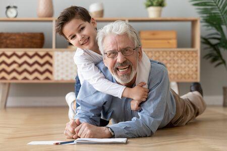 Gelukkig twee 2 generaties familie oude grootvader en schattige kleine jongen kleinzoon tekenen met potloden liggend op warme verwarmde houten vloer samen, glimlachend senior opa spelen met kleinkind camera kijken