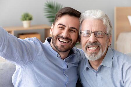Happy two generations men old father laughing embracing young son take selfie shoot vlog together on phone looking at camera, senior dad hug adult man having fun making self portrait, mobile cam view