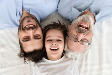 Happy multi 3 three generation family lying in row looking at camera, smiling child boy son grandson, young adult father and old senior grandfather laughing bonding, close up portrait, above top view Stockfoto