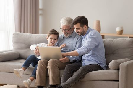 Happy three 3 age multi generation men family old grandfather young adult grown son father and child boy grandson having fun using laptop computer spend time browsing internet at home sit on sofa Stockfoto