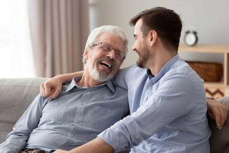 Happy two generations male family laugh enjoy talking bonding embracing sit on sofa at home, old senior father and young adult grown son relaxing having fun hugging chatting on couch on fathers day