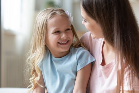 Head shot happy adorable little preschool girl talking with positive mommy. Smiling young single mother hugging cuddling embracing small cute daughter, enjoying tender moment together at home.