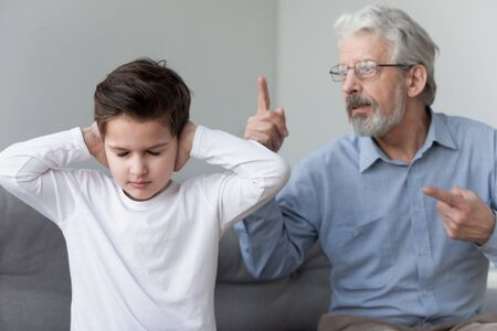 Angry old grandpa shouting at little grandson close ears ignore mad senior grandfather pointing fingers punish scold stubborn fussy grandkid for bad behavior, family conflicts, generation gap concept