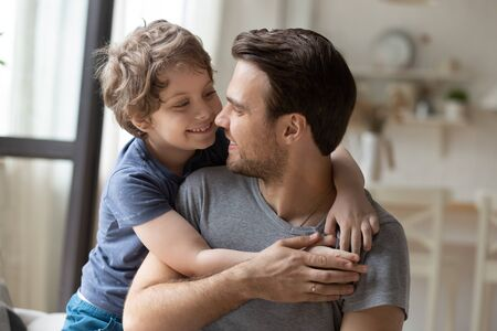 Joyful little preschool boy hugging from back smiling young father, head shot close up portrait. Happy small child playing with positive daddy, enjoying weekend time together in living room at home.