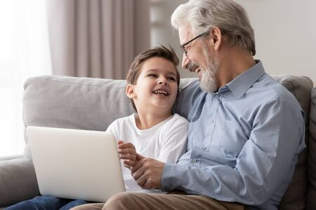 Happy old grandfather and little cute grandson laughing enjoying using laptop together sit on sofa, two age generations grandkid boy having fun with senior grandpa spend time with computer at home Stockfoto