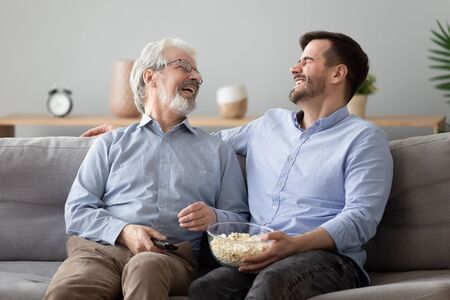 Happy two generations male family laugh enjoy talk watching funny comic tv show, cheerful old senior father and young adult son hold snack remote control bonding relax view television sit on sofa