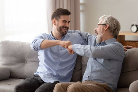 Happy family old senior father embracing young adult grown son giving fist bump sit on sofa having fun laughing bonding expressing two generations men friendship, trust understanding respect concept
