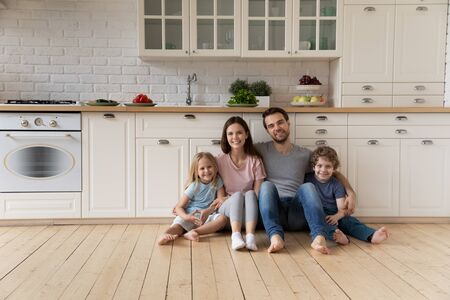 Portrait of happy young family couple sitting on wooden floor at kitchen with cute little kids siblings. Smiling positive father mother and small children looking at camera, enjoying weekend time. Stockfoto