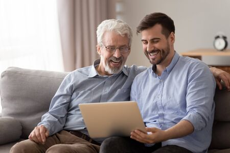 Happy two age generation family senior father and adult son having fun enjoy using laptop at home sit on couch, laughing old dad with young man bonding watching funny video looking at computer screen Stockfoto