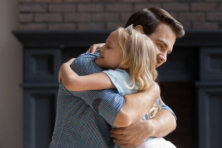 Side view head shot little happy adorable preschool blonde girl cuddling hugging embracing young smiling father. Handsome daddy supporting bonding small cute daughter, enjoying tender moment together. Stockfoto