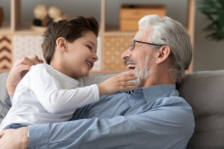 Cute little boy grandson having fun playing laughing bonding with smiling old grandfather embracing sit on couch together, happy 2 two generation family grandpa and small grandchild cuddling at home Stockfoto
