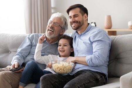 Happy multi three 3 generation men family hold snack remote control watch tv show sit on sofa together, little boy son grandson young father and old grandfather laugh view television at home on couch