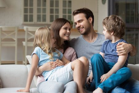Happy young family couple keeping on lap little cute preschool children siblings. Smiling millennial parents enjoying weekend time together in comfortable living room with small son and daughter.