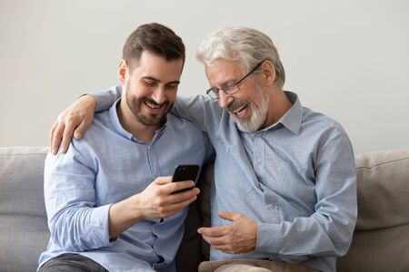 Happy two age generations men family old father embracing young grown adult son having fun, enjoying using smart phone bonding watching funny social media video using mobile apps at home sit on sofa