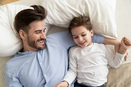 Affectionate family young father embracing cute kid son lying on bed together, little child boy and dad relaxing lay on comfortable mattress in bedroom playing bonding enjoy funny moments, top view Stockfoto