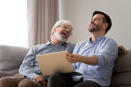 Happy male two generations family, old senior father and positive young grown adult son bonding laughing watching funny comedy on laptop having fun together using computer relaxing sit on sofa at home Stockfoto