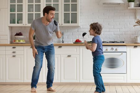 Full length overjoyed young father with happy little school age boy son holding soup ladles as microphones, singing, dancing, having fun, enjoying family weekend together in modern kitchen at home.