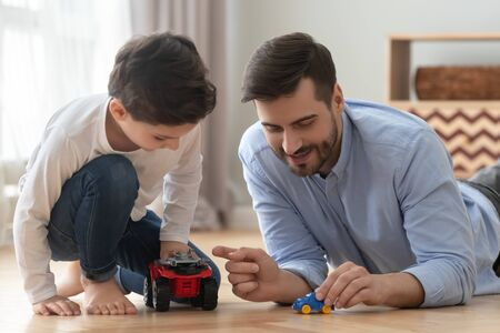 Playful happy young single father and cute little son racing holding toy cars on warm heated floor at home, small preschool child boy having fun bonding with dad playing funny game activity together Stockfoto