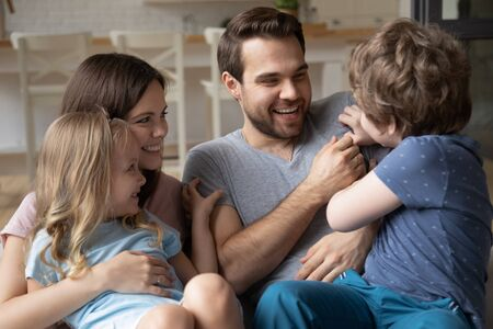 Head shot smiling young mother keeping little daughter on lap, watching laughing son tickling happy father on comfortable sofa at home. Overjoyed parents enjoying leisure weekend time with small kids. Stockfoto