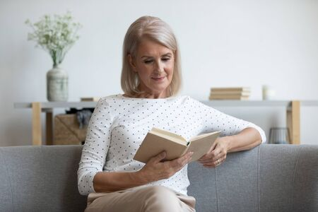 Relaxed beautiful mature woman reading book, sitting on comfortable couch, calm satisfied older female enjoying interesting literature, favorite novel or poetry, resting on weekend at home