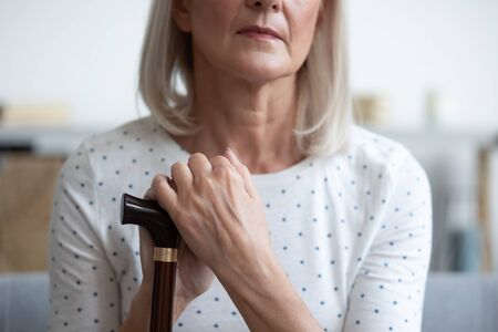 Unhappy mature woman holding hands on walking stick close up, problem with health, sitting on couch and resting, lonely older female using wooden cane during rehabilitation, older people healthcare