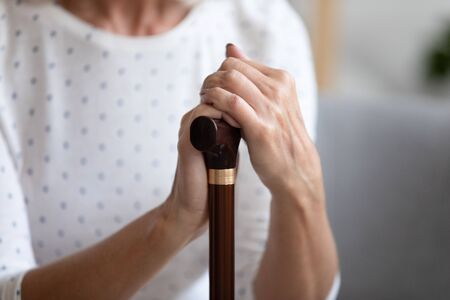 Close up lonely older woman holding hands on walking stick, problem with health, sitting on couch and resting, older female using wooden cane during rehabilitation, older people healthcare