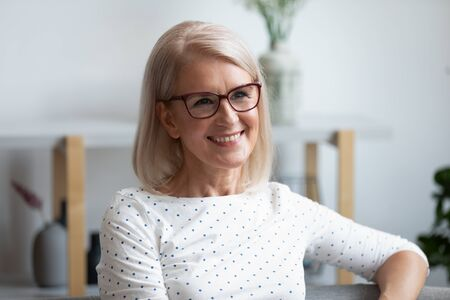 Head shot portrait close up smiling mature woman wearing glasses looking in distance, dreaming, thinking of future, older female with healthy smile sitting on couch at home, posing for photo Stockfoto