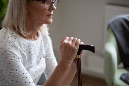 Cropped photo upset mature woman in glasses holding cane, thinking about future, disabled mature female sitting alone, using walking stick during rehabilitation, older people healthcare concept Stockfoto