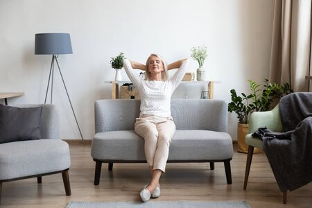 Calm older woman relaxing on comfortable sofa at home, happy mature female with hands behind head enjoying weekend, stretching on couch, resting and daydreaming, leaning back, no stress concept Stockfoto
