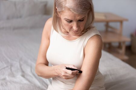 Focused mature woman measuring glucose level, blood sugar ranges in the morning, using lancet pen, sitting on bed, unhealthy mature female using blood glucose meter, diabetes, healthcare concept