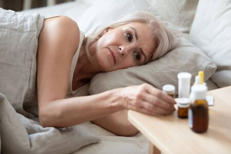 Unhealthy older woman taking pills from bedside table close up, unhappy mature female lying in bed, taking medicine from cold or insomnia, suffering from flu or seasonal fever, treatment concept 写真素材