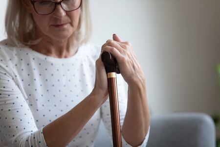 Unhappy lonely mature woman in glasses holding hands on wooden walking stick close up, sitting and resting on couch, feeling unwell, disabled older female using cane during rehabilitation