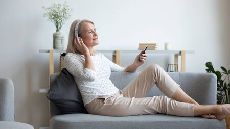 Mature woman in headphones enjoying music, using phone, peaceful satisfied older female with closed eyes relaxing on comfortable couch at home, listening to favorite song, leisure concept