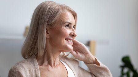 Zbliżenie portret profilowy uśmiechnięta dojrzała kobieta marząca, myśląca o dobrej przyszłości, piękna emerytowana starsza kobieta ze zdrowym uśmiechem zębów patrząca w dal, czująca się usatysfakcjonowana, naturalne piękno