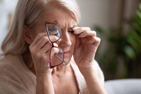Mujer mayor cansada quitándose los anteojos, sintiendo fatiga ocular, tocando los párpados de cerca, infeliz mujer madura agotada que sufre de síndrome de ojos secos, concepto de problema de salud visual