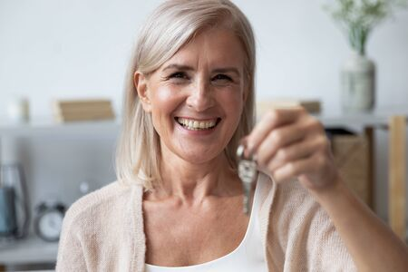 Close up head shot portrait happy older woman holding key from own apartment, looking at camera, excited mature female owner moving into new house, satisfied client customer purchase real estate