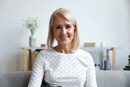 Head shot portrait close up smiling mature woman looking at camera, sitting on couch at home, beautiful older female grandmother making video call, teacher holding online lesson or recording vlog Stockfoto