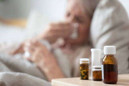 Unhealthy mature woman suffering from flu, cold or seasonal virus, allergy, meds on bedside table in bedroom close up, exhausted older female lying in bed, recovery and treatment concept