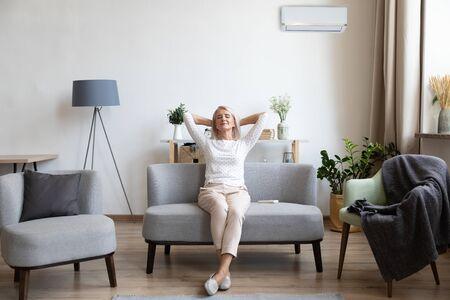 Entspannte, zufriedene ältere Frau, die sich auf der Couch im Klimaanlagenraum zurücklehnt, glückliche friedliche reife Frau mit Händen hinter dem Kopf, die zu Hause auf dem Sofa ruht, frische Luft genießt, atmen