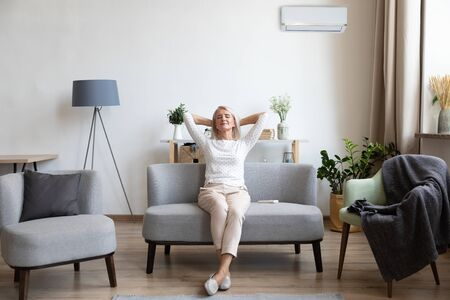 Femme âgée détendue et satisfaite assise appuyée sur un canapé dans la salle de climatisation, femme mature paisible et heureuse avec les mains derrière la tête reposant sur un canapé à la maison, profitant de l'air frais, respirant