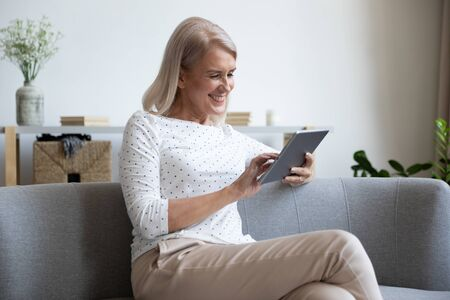 Smiling mature woman using computer tablet at home, happy older female sitting on couch, holding electronic device, looking at screen, reading news in social network, shopping or chatting online