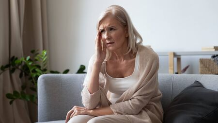 Unhappy mature woman touching head, feeling strong headache, sitting on couch at home alone, upset older female suffering from migraine or high blood pressure, health problem concept