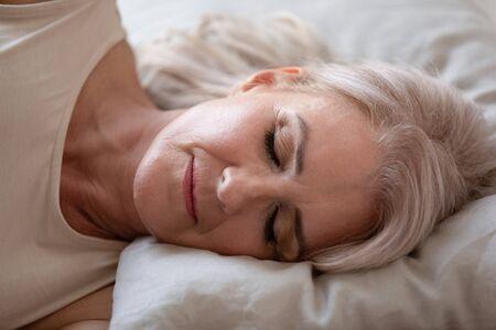 Entspannte schöne reife Frau, die in einem bequemen Bett schläft, Nahaufnahme, friedliche hübsche ältere Frau mit geschlossenen Augen, die im Schlafzimmer ruht, frische Bettwäsche genießt und auf einem weichen Kissen liegt