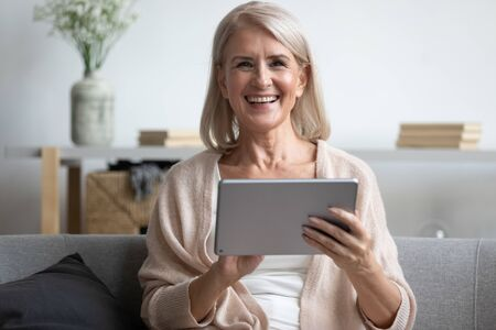 Head shot portrait close up happy mature woman using computer tablet, looking at camera, laughing at funny joke or video in social network, older female holding electronic device, sitting on couch