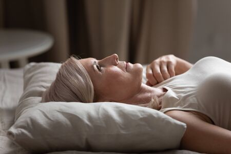 Sleepless mature woman with open eyes lying on soft pillow close up, suffering from insomnia, lack of sleep, older female lying in bed in the morning, looking up, thinking, early awakening Stockfoto