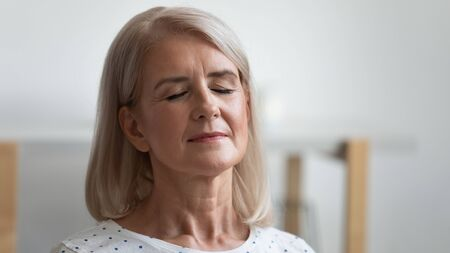 Close up calm peaceful mature woman relaxing with closed eyes, serene relaxed older retired female breathing deep, meditating, resting at home, enjoying weekend, free time, no stress concept