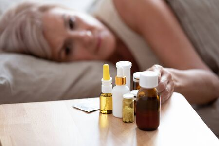 Unhealthy mature woman lying in bed, taking medicine from cold or insomnia, unhappy older female suffering from flu or seasonal fever, treatment concept, pills and meds on bedside table close up Standard-Bild